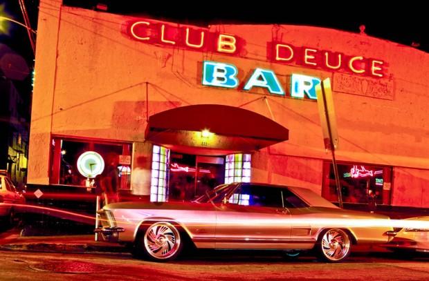 Un 1965 Buick Riviera estacionado frente a Mac club Deuce Bar, un famoso Miami Beach abrevadero y bar de buceo donde celebridades y supermodelos se codean con las damas de bolsa y vagabundos.  El edificio es una mezcla de la arquitectura de la Florida Renacimiento Mediterráneo con el Art Deco toca, tales como el tratamiento de la puerta de ladrillo de vidrio iluminada.  Fotografiado en junio de 2001.
